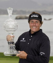 Phil Mickelson holds his trophy on the 18th green of the Pebble Beach Golf Links after winning the AT&T Pebble Beach National Pro-Am golf tournament in Pebble Beach, Calif., Sunday, Feb. 12, 2012. Mickelson won the tournament after shooting a 8-under-par 64 to finish at total 17-under-par. (AP Photo/Eric Risberg)
