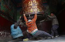 Children play with a Buddhist prayer wheel at the Boudhanath Stupa in Katmandu, Nepal, Thursday, Feb. 16, 2012. (AP Photo/Niranjan Shrestha)