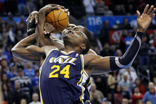 Utah Jazz forward Paul Milllsap (24) fights for a rebound with Oklahoma City Thunder forward Serge Ibaka, center, of the Republic of Congo, and Jazz center Al Jefferson, rear, in the first quarter of an NBA basketball game in Oklahoma City, Tuesday, Feb. 14, 2012. Oklahoma City won 111-85. (AP Photo/Sue Ogrocki)