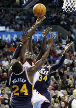 Oklahoma City Thunder center Kendrick Perkins, center, shoots while fouled by Utah Jazz guard C.J. Miles (34) and defended by forward Paul Milllsap (24) in the second quarter of an NBA basketball game in Oklahoma City, Tuesday, Feb. 14, 2012. (AP Photo/Sue Ogrocki)