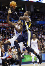 Utah Jazz forward Paul Milllsap, right, shoots in front of Oklahoma City Thunder forward Serge Ibaka, left, of the Republic of Congo, in the third quarter of an NBA basketball game in Oklahoma City, Tuesday, Feb. 14, 2012. Oklahoma City won 111-85. (AP Photo/Sue Ogrocki)