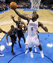 Oklahoma City Thunder center Kendrick Perkins (5) grabs a rebound in front of Utah Jazz forward Paul Milllsap, left, and guard Raja Bell (19) in the third quarter of an NBA basketball game in Oklahoma City, Tuesday, Feb. 14, 2012. Oklahoma City won 111-85. (AP Photo/Sue Ogrocki)