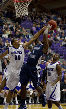 In this photo provided by the University of Portland, BYU's Charles Abouo (1) shoots over Portland's Kevin Bailey (00) and Derrick Rogers (15) during the first half of their NCAA college basketball game in Portland, Ore., Saturday, Feb. 4, 2012. (AP Photo/University of Portland, Steven Gibbons)