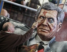 Dieter Wenger of the carnival club of Mainz works on the face of a paper machee figure depicting German President Christian Wulff in a garage in Mainz, Germany, Friday, Feb. 17, 2012. Wulff resigned  from his post on Friday. (AP Photo/Michael Probst)