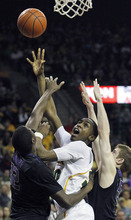 Baylor's Quincy Miller (30) shoots between Kansas State's Jamar Samuels (32) and Will Spadling (55) during the first half of an NCAA college basketball game, Saturday Feb. 18, 2012, in Waco, Texas. (AP Photo/LM Otero)