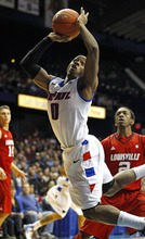 DePaul's Worrel Clahar, center, shoots in front of Louisville's Russ Smith, right,  during the first half of an NCAA college basketball game in Rosemont, Ill., on Saturday, Feb. 18, 2012.  (AP Photo/Kamil Krzaczynski)