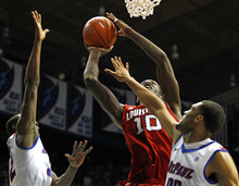 Louisville's Gorgui Dieng, center, goes to the basket between DePaul's Charles McKinney, left and DePaul's Donnavan Kirk, right, during the first half of an NCAA college basketball game in Rosemont, Ill., on Saturday, Feb. 18, 2012.  (AP Photo/Kamil Krzaczynski)