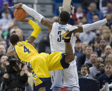 Connecticut's Alex Oriakhi, right, fouls Marquette's Todd Mayo during the first half of an NCAA college basketball game in Hartford, Conn., Saturday, Feb. 18, 2012.  (AP Photo/Jessica Hill)