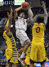 Connecticut's Jeremy Lamb, center, drives to the basket while guarded by Marquette's Vander Blue, left, and Jamil Wilson, right, during the first half of an NCAA college basketball game in Hartford, Conn., Saturday, Feb. 18, 2012.  (AP Photo/Jessica Hill)