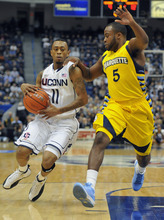 Connecticut's Ryan Boatright, left, is guarded by Marquette's Junior Cadougan in the first half of an NCAA college basketball game in Hartford, Conn., Saturday, Feb. 18, 2012.  (AP Photo/Jessica Hill)