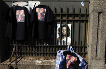 Whitney Houston merchandise is displayed for sale as fans gather a few blocks from the New Hope Baptist Church before the singer's funeral in Newark, N.J., Saturday, Feb. 18, 2012. (AP Photo/Jason DeCrow)