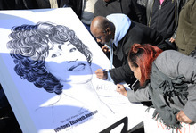 Fans sign a poster showing a picture of Whitney Houston near a funeral service for the singer at the New Hope Baptist Church in Newark, N.J., Saturday, Feb. 18, 2012. (AP Photo/Charles Sykes)
