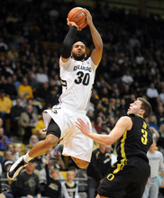 Carlon Brown of Colorado shoots over Garrett Sim of Oregon, during the first half of  of an NCAA college basketball game Saturday Feb. 4, 2012 in Boulder, Colo. (AP Photo/Daily Camera, Cliff Grassmick)