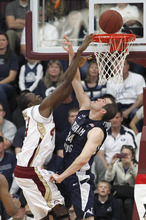 Santa Clara's Yannick Atanga (44) takes a shot over Brigham Young's Noah Hartsock (34) during the first half of an NCAA college basketball game in Santa Clara, Calif., Saturday, Feb. 18, 2012. (AP Photo/Tony Avelar)