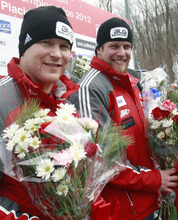 Canada's pilot Lyndon Rush, left, and brakeman Jesse Lumsden react after their second-place finish in the men's two-man bobsled world championships in Lake Placid, N.Y., on Sunday, Feb. 19, 2012. (AP Photo/Mike Groll)