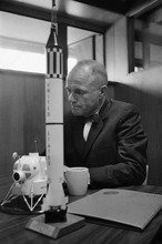 FILE - In this Feb. 8, 1963 file photo, astronaut John Glenn sits with models of the Mercury spaceship atop its launch rocket and a lunar module, representing the past and the future of space exploration as he talks about the first anniversary of his historic flight. (AP Photo/Ed Kolenovsky)