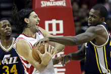 Utah Jazz's Paul Millsap, right, forces a jump ball with Houston Rockets' Luis Scola, left, of Argentina, during the second half of an NBA basketball game, Sunday, Feb. 19, 2012, in Houston. The Rockets won 101-85. (AP Photo/David J. Phillip)