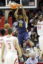 Utah Jazz's Derrick Favors (15) hangs on the rim after dunking the ball as Houston Rockets' Patrick Patterson (54) defends during the second quarter of an NBA basketball game, Sunday, Feb. 19, 2012, in Houston. (AP Photo/David J. Phillip)