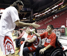 Houston Rockets' Luis Scola, left, of Argentina, high-fives 13-year-old Nicholas Tijerina, right, before their game against the Utah Jazz, Sunday, Feb. 19, 2012, in Houston. Tijerina and his family were guests of the Rockets and received a behind-the-scenes tour while meeting with players. Tijerina is one of two victims who were involved in an accidental shooting this past December as they were trying out for their school's basketball team on an outdoor court in Edinburg, Texas. He was left paralyzed and has been receiving medical rehabilitation treatment in Houston. (AP Photo/David J. Phillip)