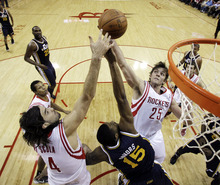 Houston Rockets' Chandler Parsons (25) and Luis Scola (4), of Argentina, reach for a rebound along with Utah Jazz's Derrick Favors (15) during the first quarter of an NBA basketball game, Sunday, Feb. 19, 2012, in Houston. (AP Photo/David J. Phillip)
