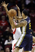 Utah Jazz's Devin Harris (5) looks to pass the ball as Houston Rockets' Kyle Lowry, left, defends during the first quarter of an NBA basketball game, Sunday, Feb. 19, 2012, in Houston. (AP Photo/David J. Phillip)