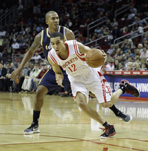 Houston Rockets' Kevin Martin (12) drives around Utah Jazz's Raja Bell during the first quarter of an NBA basketball game Sunday, Feb. 19, 2012, in Houston. (AP Photo/David J. Phillip)