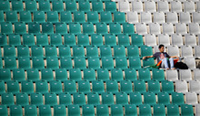 A lone spectator watches an Olympic qualifier field hockey match between Poland and Italy in New Delhi, India, Tuesday, Feb. 21, 2012. (AP Photo/Saurabh Das)