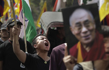 A portrait of the Dalai Lama is seen to the right as exile Tibetan students shout slogans during a protest against the Chinese government, in New Delhi, India, Tuesday, Feb. 21, 2012. A young Tibetan Buddhist monk set himself on fire to protest Chinese rule, becoming at least the 21st to do so in the past year, and more than 1,000 people were trying to prevent police from taking his body, an overseas Tibet support group reported Monday. (AP Photo/Manish Swarup)