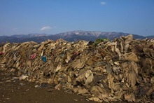 Clothing, lying in heaps at the site of a neighborhood destroyed by the tsunami, is piled up by clearing crew in Rikuzentakata, Iwate Prefecture, northern Japan on Tuesday, Feb. 21, 2012. Cleanup continues to remove the debris left by the March 11, 2011 tsunami and separate it according to material or category such as clothing, steel, wood, cars, tires, and personal items. (AP Photo/David Guttenfelder)