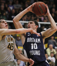 BYU's Matt Carlino (10) reaches up to shoot as San Francisco's Cody Doolin defends during the first half of an NCAA college basketball game in San Francisco, Thursday, Feb. 16, 2012. BYU beat San Francisco 85-84. (AP Photo/George Nikitin)