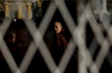 A Myanmar Buddhist monk is seen through steel railings during a prayer session during the 2,600th anniversary celebrations of Shwedagon Pagoda in Yangon, Myanmar, Wednesday, Feb. 22, 2012. Gongs chimed as thousands of people in ceremonial costumes walked barefoot Wednesday through the marble walkways of Myanmar's most sacred Buddhist shrine in an annual festival that was banned for more than 20 years under the former military government. (AP Photo/Altaf Qadri)