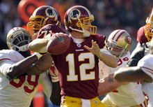 Washington Redskins quarterback John Beck (12) looks for a receiver as he is pressured by the San Francisco 49ers in the first half of an NFL football game in Landover, Md., Sunday, Nov. 6, 2011. (AP Photo/Cliff Owen)
