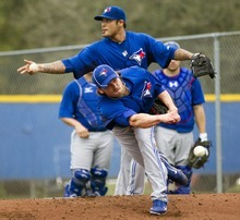 Toronto Blue Jays Danny Farquhar, front, pitches as Sergio Santos, rear, tosses balls back to coaches during spring training baseball in Dunedin, Fla., on Thursday, Feb. 23, 2012. (AP Photo/The Canadian Press, Frank Gunn)