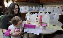 Three-year-old Skylar Swoatskey reaches for a cup of water as her mother, Kimberlie McEvoy is surrounded by the water bottles they use as she talks about the water problems on Thursday, Feb. 23, 2012, at her home in Evans City, Pa. McEvoy is one of at least 10 households in western Pennsylvania that fears their drinking water has been ruined by natural gas drilling. State officials say tests don't show that. Residents say Rex Energy Corp. has sent letters notifying them it will no longer deliver drinking water to the households after Feb. 29.(AP Photo/Keith Srakocic)