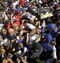 Texas Rangers pitcher Yu Darvish, at right, from Japan, signs autographs during spring training baseball Thursday, Feb. 23, 2012, in Surprise, Ariz. (AP Photo/Charlie Riedel)