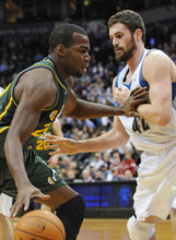 Utah Jazz' Paul Millsap, left, holds Minnesota Timberwolves' Kevin Love at bay as he drives in the first half of an NBA basketball game Wednesday, Feb. 22, 2012, in Minneapolis. (AP Photo/Jim Mone)