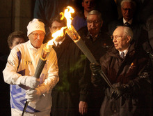 Mormon apostle Neal A. Maxwell lights his torch from the one held by LDS Church President Gordon B. Hinckley during the start of the 2002 Salt Lake Olympics.