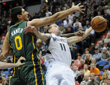 Utah Jazz' Enes Kanter of Turkey, left, defends as Minnesota Timberwolves' J.J. Barea is fouled by another player in the second half of an NBA basketball game Wednesday, Feb. 22, 2012, in Minneapolis. The Timberwolves won 100-98. Barea led his team's scoring with 22 points. (AP Photo/Jim Mone)