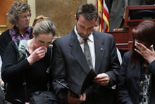 Francisco Kjolseth  |  The Salt Lake Tribune Christopher Suter, center, father of fallen soldier Spc. Preston J. Suter of the 709th Military Police Battalion who died in Afghanistan on July 5, 2011, reads an official citation honoring Utah's Fallen Soldiers. At left is Preston's aunt Kathleen Suter and his step mom Dixie Suter at right. The citation was presented to the families representing the six fallen soldiers who all died on duty in Afghanistan in 2011, in front of the house of representatives at the Utah State Capitol on Thursday, Feburary 23, 2012.