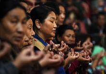 Tibetan women offer prayers at a Tibetan Monastery during the third day of