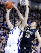 Utah State forward Morgan Grim (21) has his shot blocked by Idaho center Kyle Barone (33) during their NCAA college basketball game on Friday, Feb. 24, 2012, in Logan, Utah. (AP Photo/The Herald Journal, Eli Lucero)