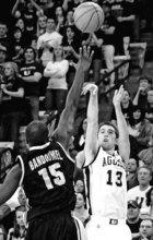 Utah State guard Preston Medlin (13) shoots a 3-pointer over Idaho forward Djim Bandoumel (15) during an NCAA college basketball game, Friday, Feb. 24, 2012, in Logan, Utah. Utah State won 67-50. (AP Photo/The Herald Journal, Eli Lucero)