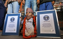 Nepal's Chandra Bahadur Dangi poses with his certificates after being declared the world's shortest living man and shortest man ever by the Guinness Book of Records at a ceremony in Katmandu, Nepal, Sunday, Feb. 26, 2012. The 72-year-old man was measured at just 21.5 inches (54.6 centimeters) tall has been declared the shortest person to be recorded by the Guinness World Records snatching the title from Junrey Balawing of the Philippines, who is 23.5 inches (60 centimeters) tall. (AP Photo/Niranjan Shrestha)