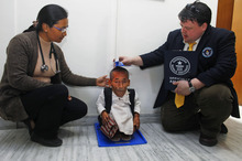 Editor in Chief of Guinness World Records Craig Glanday, right, and Dr. Kashila Pradhan, left, officially measure Nepal's Chandra Bahadur Dangi, 72, who says he's only 22 inches (56 centimeters) tall, at the CIWEC clinic in Katmandu, Nepal, Sunday, Feb. 26, 2012. Guinness World Records officials measured Dangi who hopes to be named the world's shortest man later Sunday. Dangi is hoping to snatch the title of the world's shortest man from Junrey Balawing of the Philippines, who is 23.5 inches (60 centimeters) tall. (AP Photo/Niranjan Shrestha)