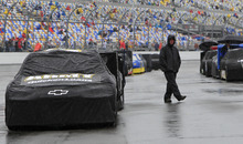 An crew member walks past race cars covered to protect them from the rain before the NASCAR Daytona 500 Sprint Cup series auto race at Daytona International Speedway in Daytona Beach, Fla., Sunday, Feb. 26, 2012. (AP Photo/John Raoux)
