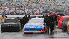Crew members push driver Elliott Sadler's car down the starting grid in the rain before the NASCAR Daytona 500 Sprint Cup series auto race at Daytona International Speedway in Daytona Beach, Fla., Sunday, Feb. 26, 2012. (AP Photo/John Raoux)