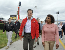 Republican presidential candidate, former Massachusetts Gov. Mitt Romney, left, walks with Florida Lt. Gov. Jennifer Carroll, right, before the NASCAR Daytona 500 Sprint Cup series auto race at Daytona International Speedway in Daytona Beach, Fla., Sunday, Feb. 26, 2012. (AP Photo/Rainier Ehrhardt)