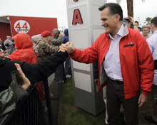 Republican presidential candidate, former Massachusetts Gov. Mitt Romney, right, greets race fans before the NASCAR Daytona 500 Sprint Cup series auto race at Daytona International Speedway in Daytona Beach, Fla., Sunday, Feb. 26, 2012. (AP Photo/John Raoux)