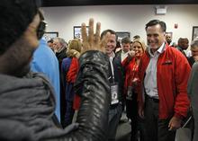 Republican presidential candidate, former Massachusetts Gov. Mitt Romney, right, greets singer Lenny Kravitz, left, during the drivers and crew chiefs meeting before the NASCAR Daytona 500 Sprint Cup series auto race at Daytona International Speedway in Daytona Beach, Fla., Sunday, Feb. 26, 2012. (AP Photo/Pool, Chris Graythen)