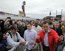 Republican presidential candidate, former Massachusetts Gov. Mitt Romney, center, greets fans as he walks through the garage area before the NASCAR Daytona 500 Sprint Cup series auto race at Daytona International Speedway in Daytona Beach, Fla., Sunday, Feb. 26, 2012. (AP Photo/Terry Renna)
